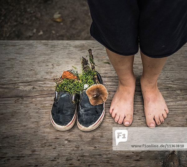 Nackte Füße eines Jungen neben Schuhen voller Natur