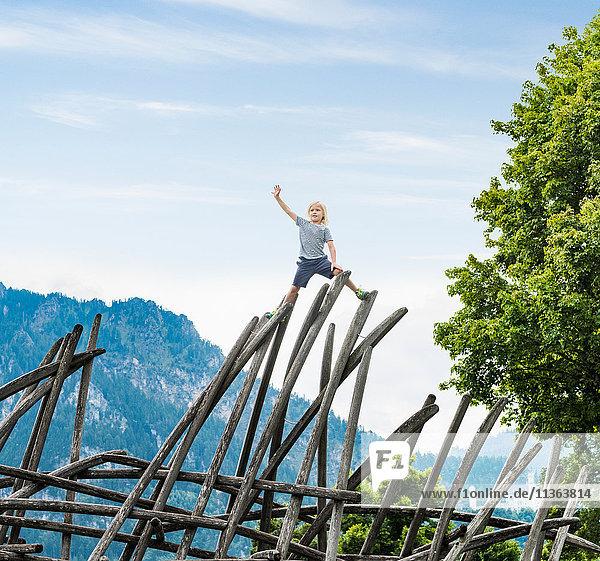 Junge steht auf einer Holzkonstruktion auf einem Spielplatz  Füssen  Bayern  Deutschland