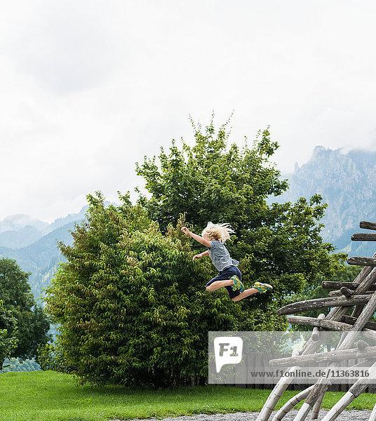 Junge in der Luft  der von einer Holzkonstruktion auf einem Spielplatz springt  Füssen  Bayern  Deutschland