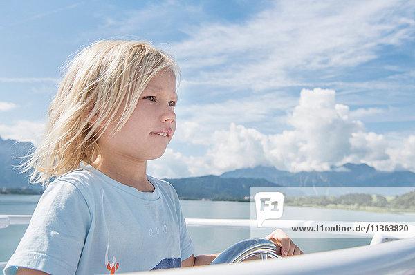 Junge steuert Boot wegschauend  Füssen  Bayern  Deutschland