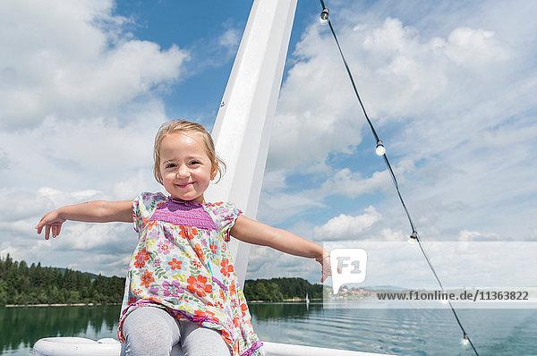 Porträt eines Mädchens auf einem Boot  das lächelnd in die Kamera schaut  Füssen  Bayern  Deutschland