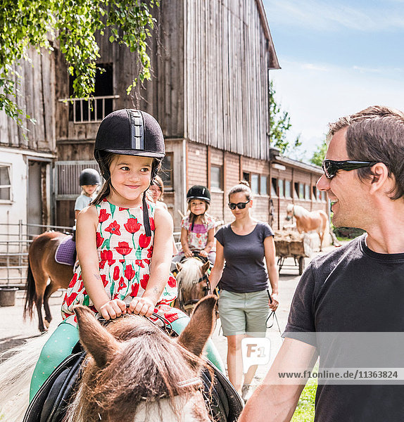 Father guiding daughter riding horse