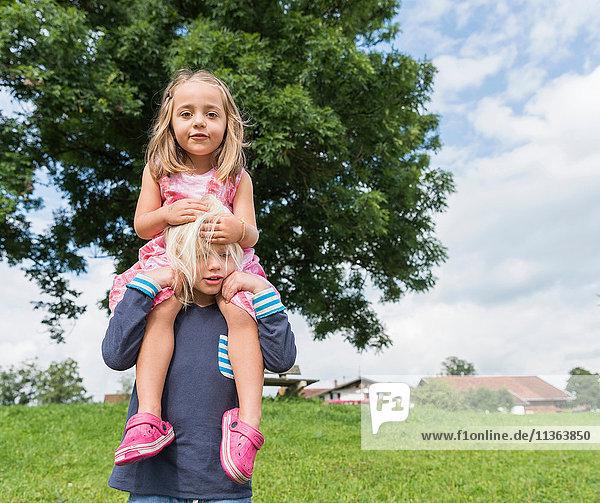 Junge trägt Schwester auf den Schultern  Füssen  Bayern  Deutschland