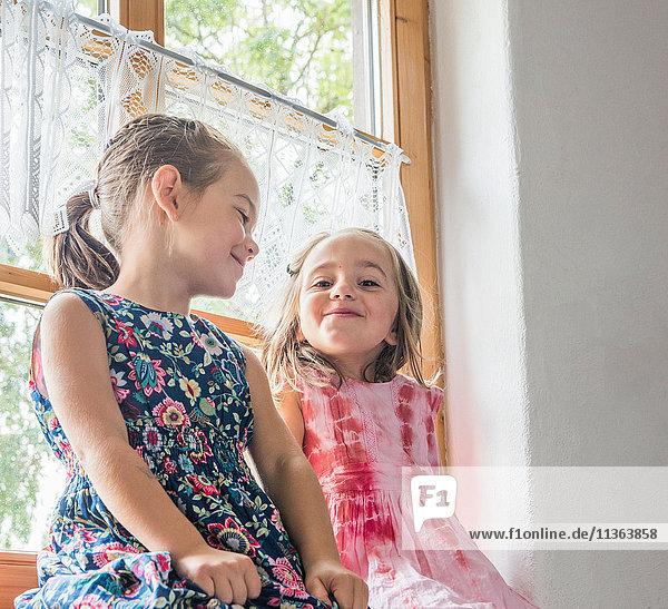 Mädchen sitzt lächelnd auf der Fensterbank
