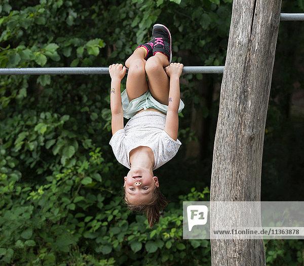 Mädchen hängt kopfüber von der Affenstange
