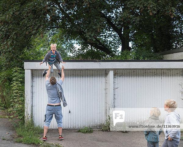 Junge springt aus der Garage in die offenen Arme des Vaters