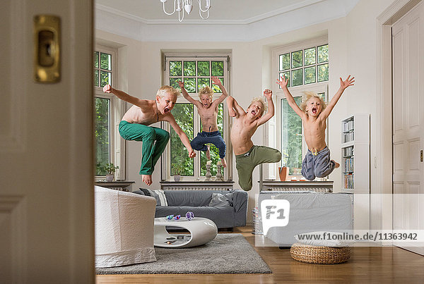 Jungen im Wohnzimmer springen in die Luft