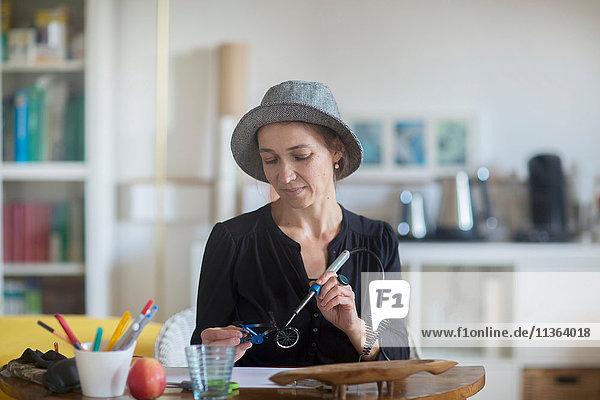 Reife Frau am Schreibtisch sitzend  mit Lötkolben