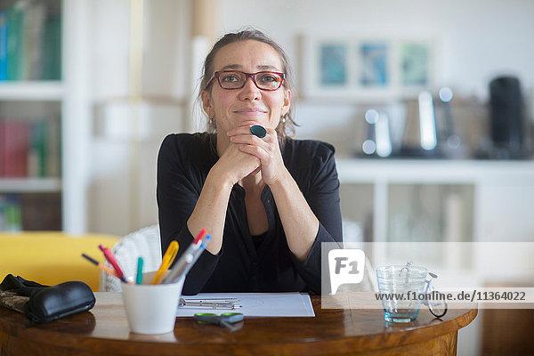 Porträt einer reifen Frau am Schreibtisch sitzend