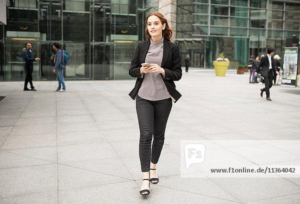 Frau  die in der Stadt spazieren geht und ein Smartphone in der Hand hält.