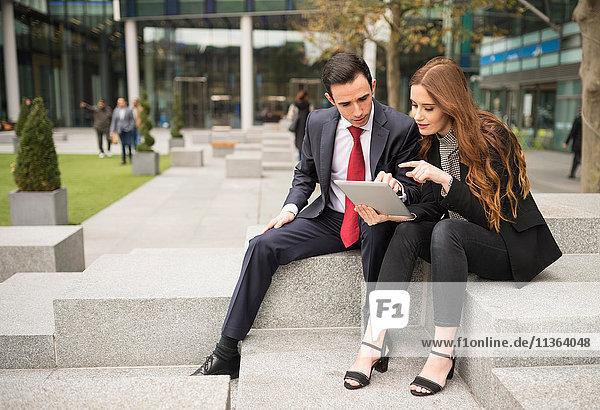 Geschäftsleute in der Stadt mit digitalem Tablett