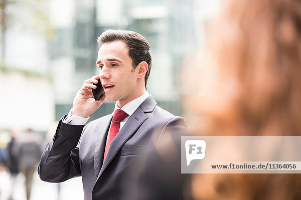 Businessman in city making telephone call