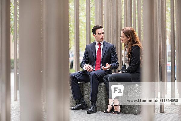 Geschäftsleute  die in der Stadt sitzen und reden.