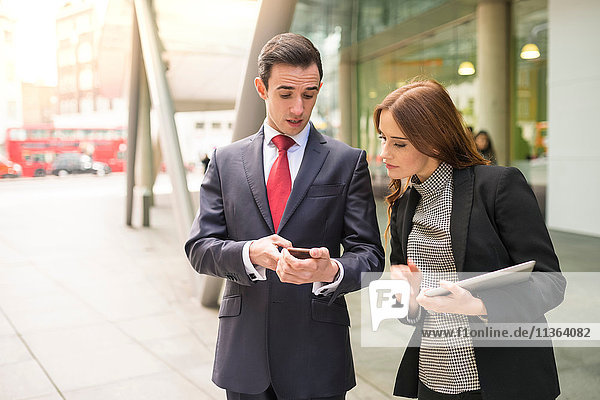 Businesspeople in city looking at smartphone talking