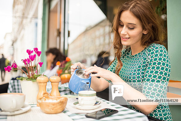 Woman at pavement cafe pouring from teapot