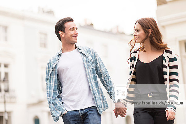 Couple walking in street face to face smiling