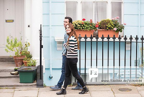 Seitenansicht des Paares  das lächelnd auf der Straße geht