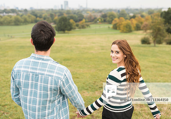 Rear view of couple holding hands in field