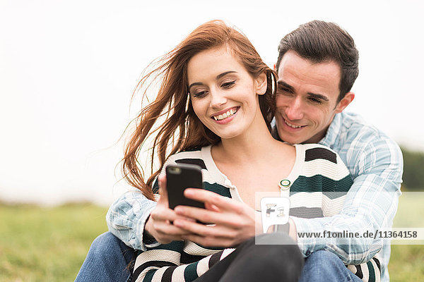 Couple sitting in field hugging looking at smartphone