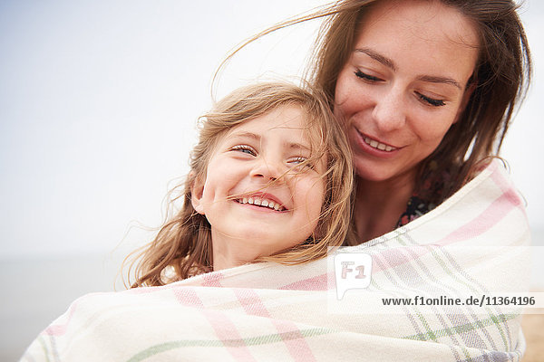 Happy mother and daughter wrapped in blanket