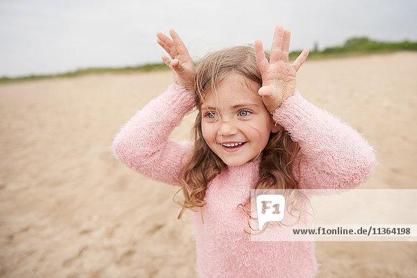 Kleines Mädchen mit Hörnern auf dem Kopf am Strand