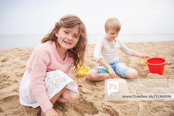 Kinder bauen Sandburg am Strand