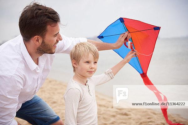 Vater und Sohn spielen Drachen am Strand