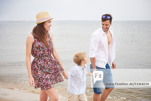 Familie hält beim Strandspaziergang Händchen