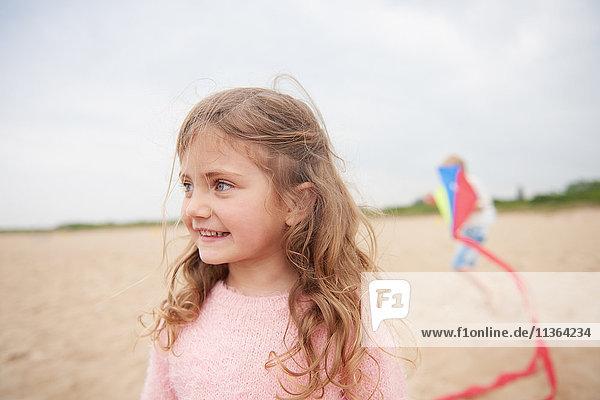 Kleines lächelndes Mädchen am Strand  Drachen spielende Person im Hintergrund