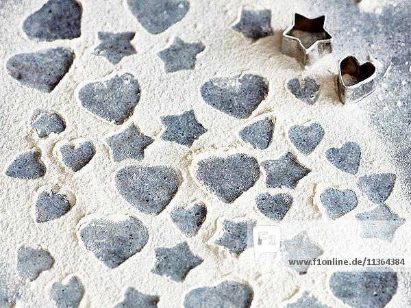 Herz- und Sternformmuster in Mehl mit Keksausstechern
