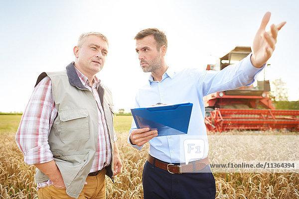 Landwirt und Geschäftsmann im Weizenfeld hält Klemmbrett und schaut weg