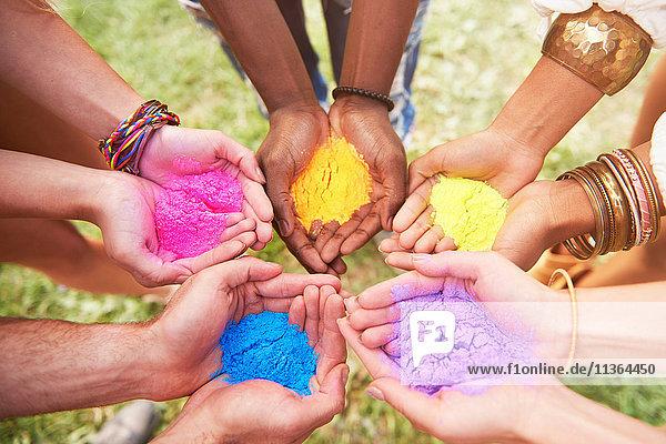 Gruppe von Freunden beim Festival  die bunte Pulverfarbe in schalenförmigen Händen halten  Nahaufnahme