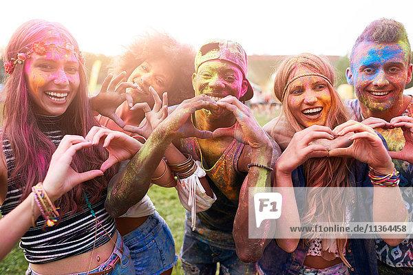 Porträt einer Gruppe von Freunden beim Festival  mit bunter Pulverfarbe überzogen  die mit den Händen Herzformen herstellt