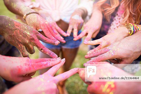 Gruppe von Freunden beim Festival  mit bunter Pulverfarbe überzogen  Finger mit Friedenszeichen verbinden  Nahaufnahme