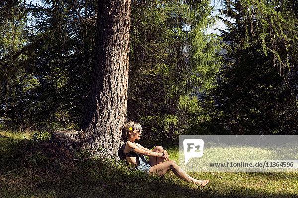 Mittlere erwachsene Frau  die sich an einen Waldbaumstamm lehnt  Sattelbergalm  Tirol  Österreich