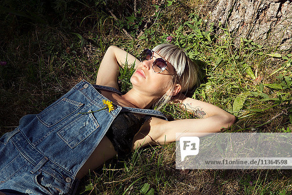 Mid adult woman lying on grass in sunlight  Sattelbergalm  Tyrol  Austria