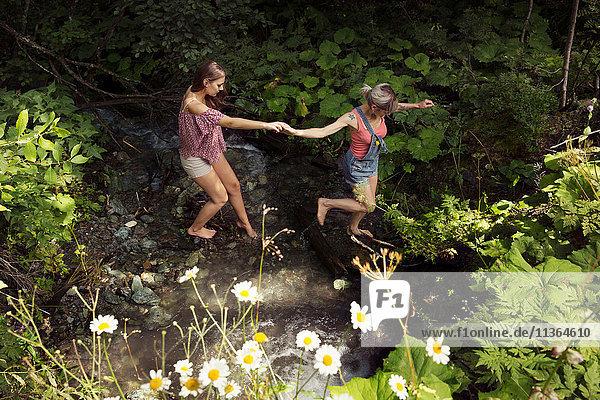 Two female friends crossing stream  Sattelbergalm  Tyrol  Austria
