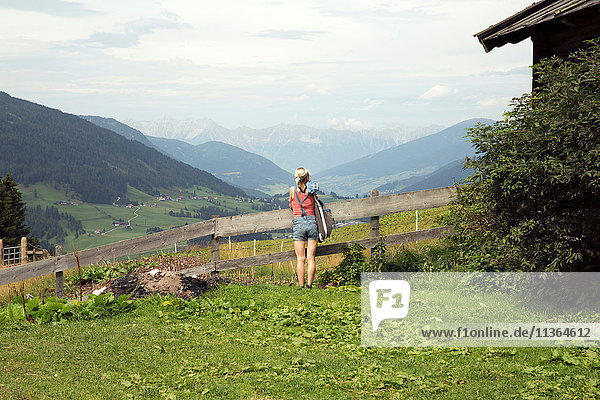 Rear view of woman looking out toward mountain landscape  Sattelbergalm  Tyrol  Austria