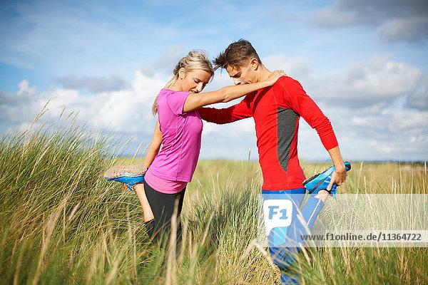 Paar im hohen Gras auf einem Bein bei Dehnungsübungen