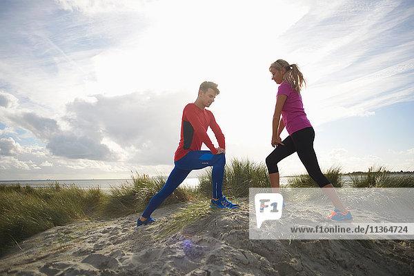 Paar auf Sanddüne  Hände auf Knie bei Dehnungsübungen