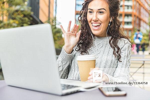 Mittlere erwachsene Frau  im Freien sitzend  Kopfhörer tragend  Laptop für Videoanrufe verwendend
