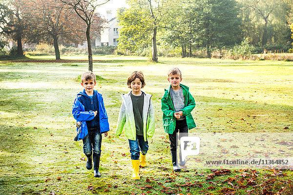 Drei Jungen  im Freien  gehen über das Feld