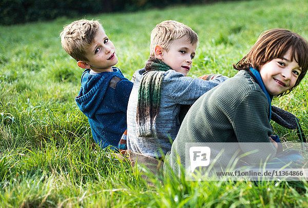 Portrait of three boys  sitting together in field  in autumn