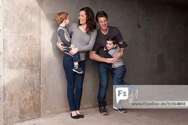 Familie steht an der Wand und lächelt