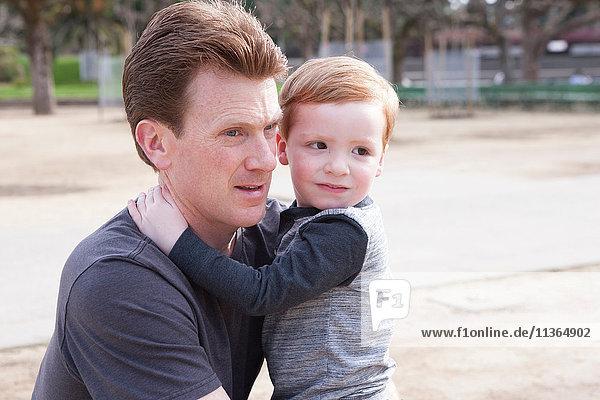 Junge umarmt Vater  besorgter Gesichtsausdruck des Jungen