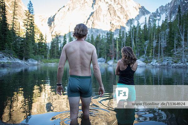 Junger Mann und Frau stehen im See  Rückansicht  Die Verzauberungen  Alpine Lakes Wilderness  Washington  USA