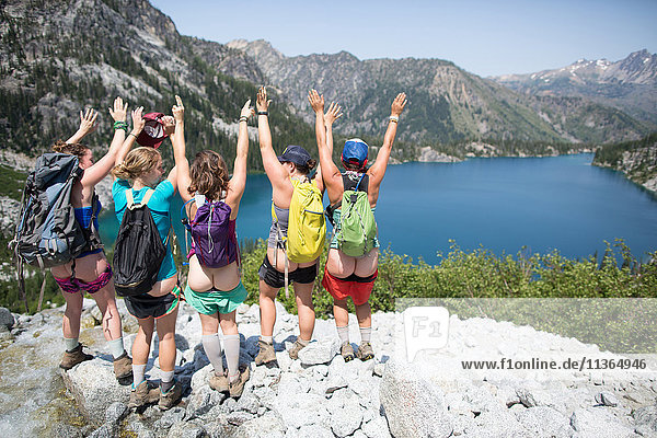 Five young women  standing on rock beside lake  arms raised  rear view  The Enchantments  Alpine Lakes Wilderness  Washington  USA