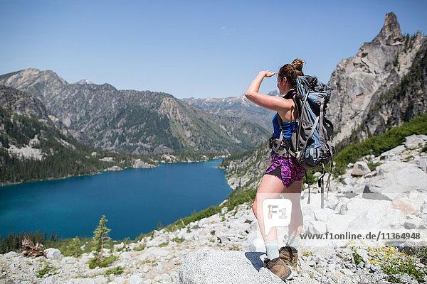 Junge Frau steht auf Felsen und schaut auf die Aussicht  Die Verzauberungen  Alpine Lakes Wilderness  Washington  USA