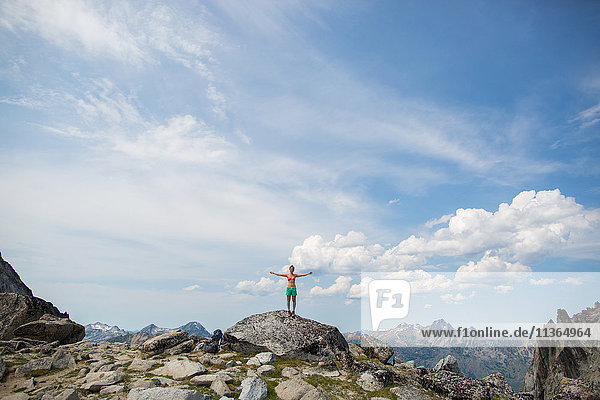 Young woman standing on rock  arms open  The Enchantments  Alpine Lakes Wilderness  Washington  USA