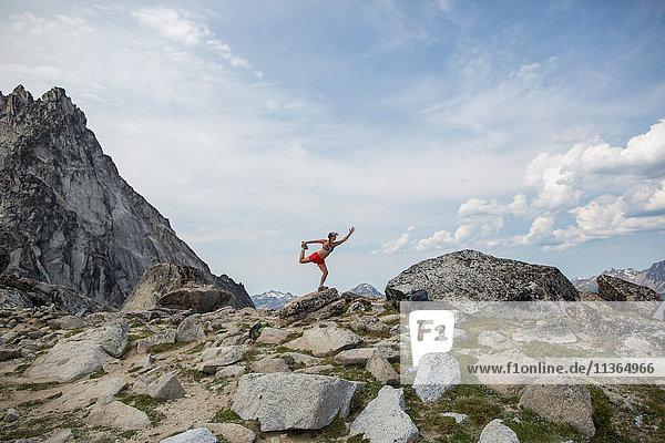 Junge Frau auf Felsen stehend  in Yoga-Pose  Die Verzauberungen  Alpine Lakes Wilderness  Washington  USA